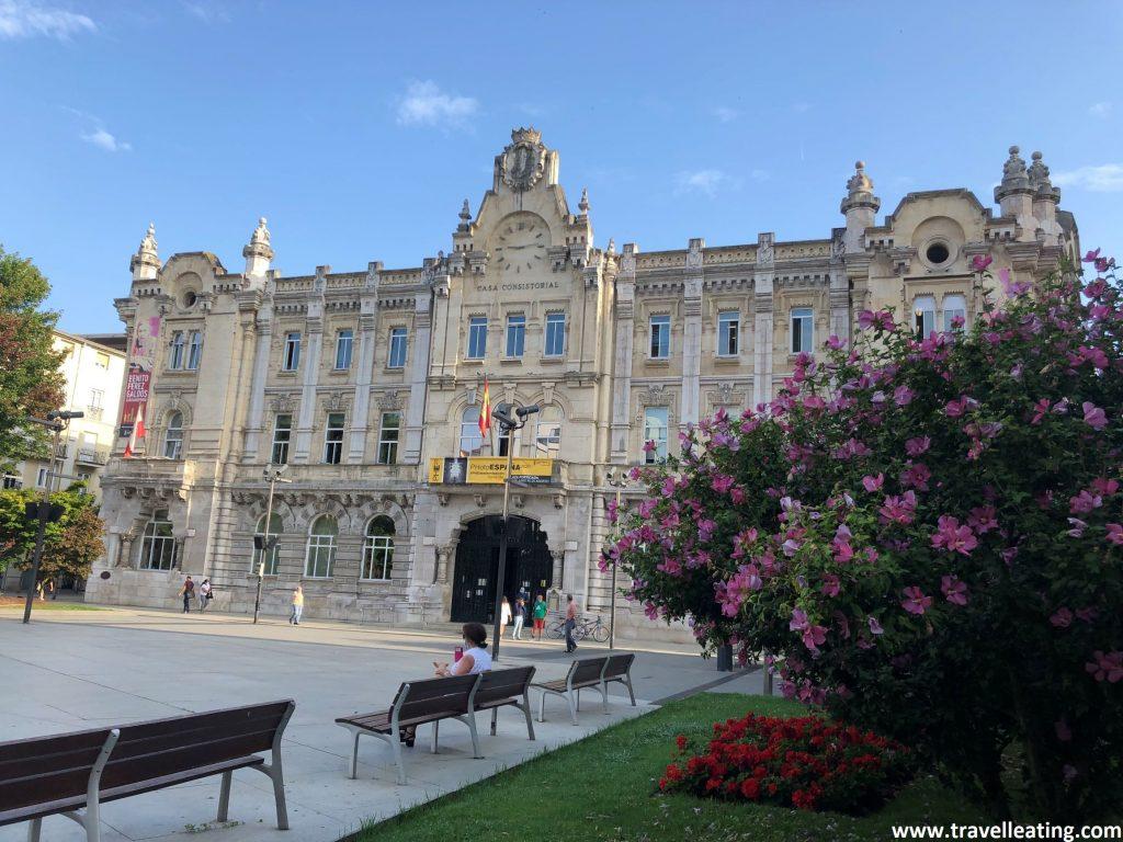 Plaza con bancos, plantas y flores, en medio  de la cual encontramos un edificio grande y elegante: el Ayuntamiento de Santander.
