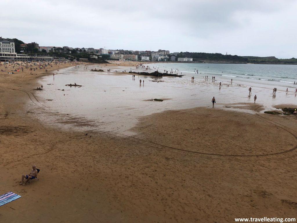Playa larga repleta de gente. Se trata de la Playa del Sardinero, uno de los imprescindibles que visitar en Santander.