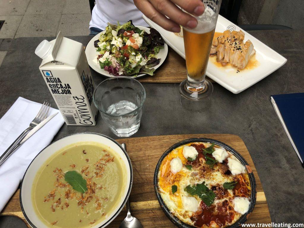 Mesa con cuatro platos: una ensalada, una crema de lechugas, un pollo al curry y una pequeña cazuela de barro con pisto y huevo gratinados. Nuestra comida en uno de los mejores restaurantes de Santander.
