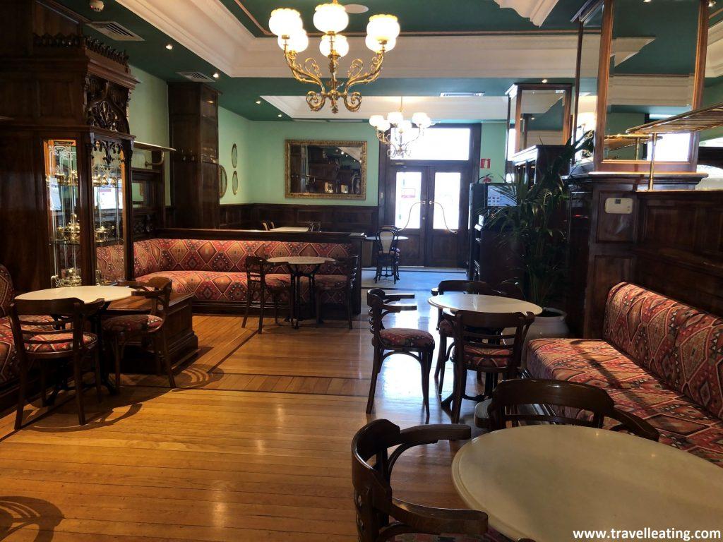 Interior de una cafetería antigua pero muy bien conservada con muebles elegantes de madera y sillones rojos.