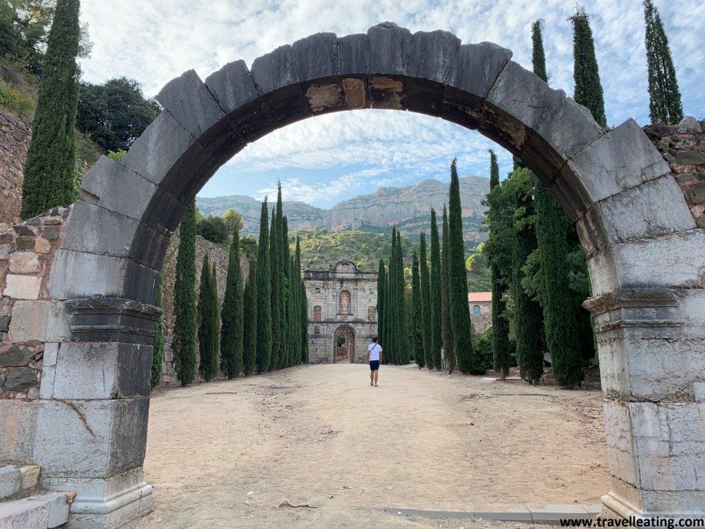 Entrada de un precioso monasterio con un arco de piedra tras el cual se extiende un pasillo franqueado por abedules. Esta cartuxa es sin duda una de las mejores cosas que ver de El Priorat.