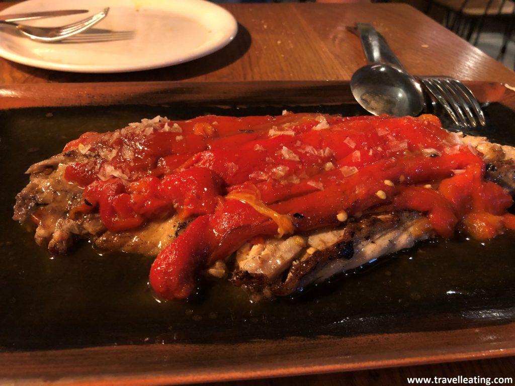 Ventresca de bonito servida con pimiento rojo por encima, ambos asada al carbón
