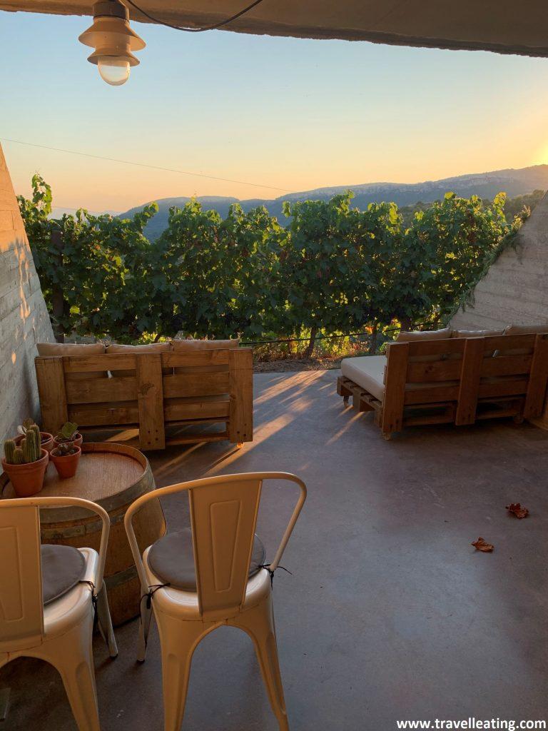 Pequeña terraza con una mesa y sillas y con sofás hechos con palets, situada frente a unas preciosas viñas. El cielo está rojizo puesto que se trata del atardecer.