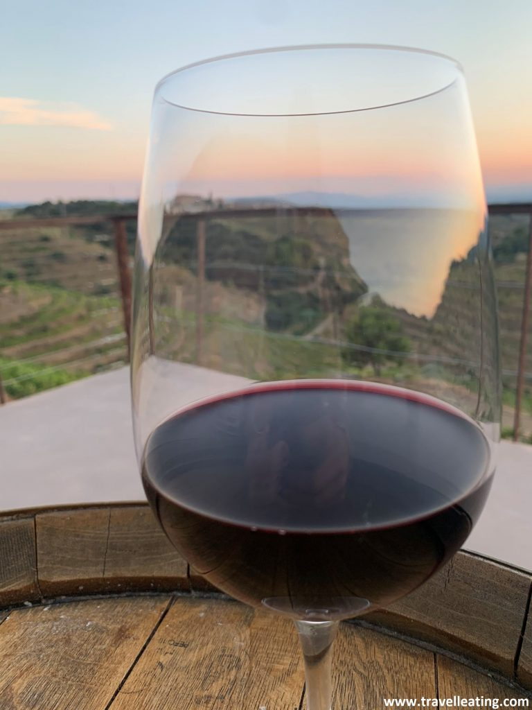 Copa con vino tinto encima de un barril dispuesto como mesa en una terraza. A través de la copa i alrededor de esta destaca el cielo con tonos rojizos de un bonito atardecer.