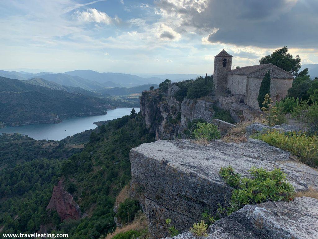 Iglesia que se alza encima de un risco. Bajo éste se observa un bonito río rodeado de montañas. Es la típica imagen de Siurana, uno de los pueblos más bonitos de Cataluña y sin duda su visita es de lo mejor que hacer en El Priorat.