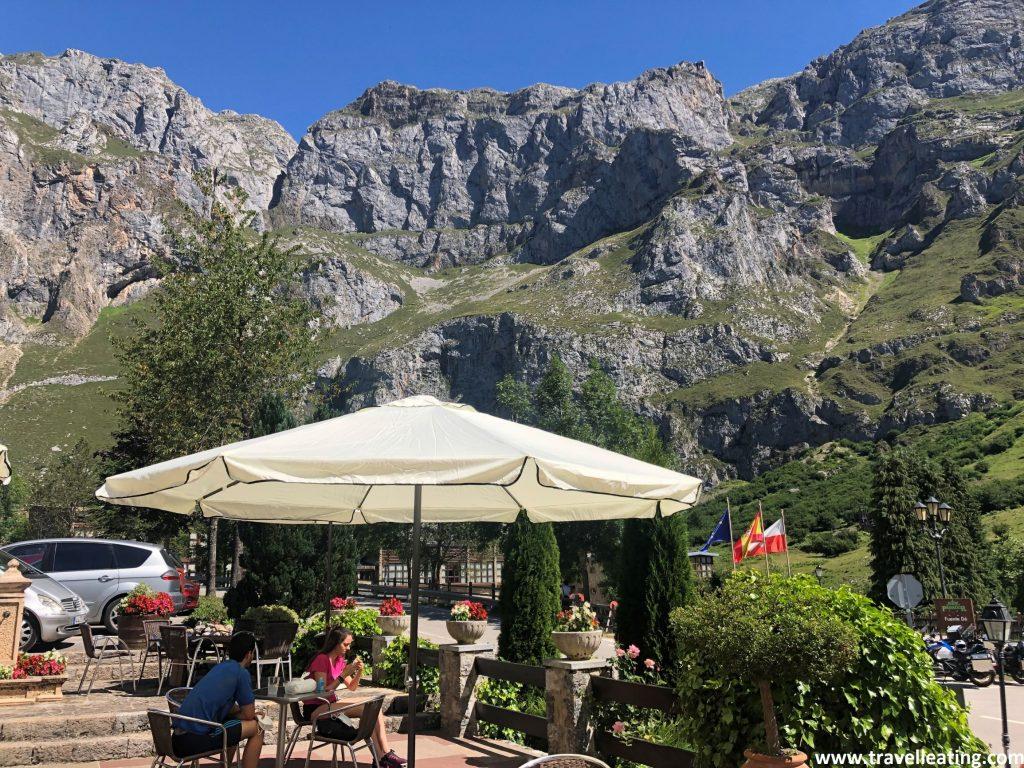 Terraza de un hotel con mesas y parasoles, decorada con plantas y rodeada de montañas.