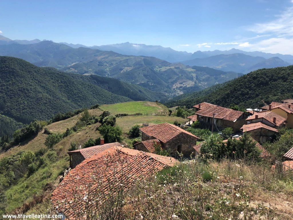 Vistas de un pueblo tradicional con casas de tejados anaranjados y paredes de piedra que se encuentra en un valle verde rodeado de montañas. Los miradores son una de las mejores cosas que ver y hacer en Liébana