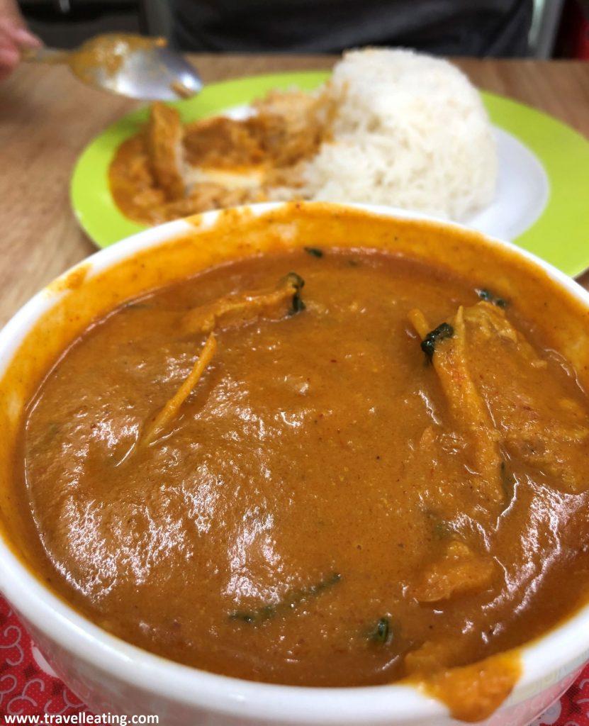 Bol de curry con pollo servido con un plato de arroz.