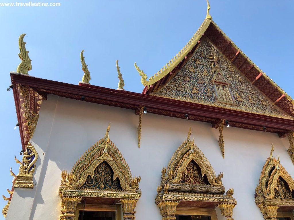 Fachada principal de un templo blanco con ornamientaciones doradas y rojas en ventanas y techo.