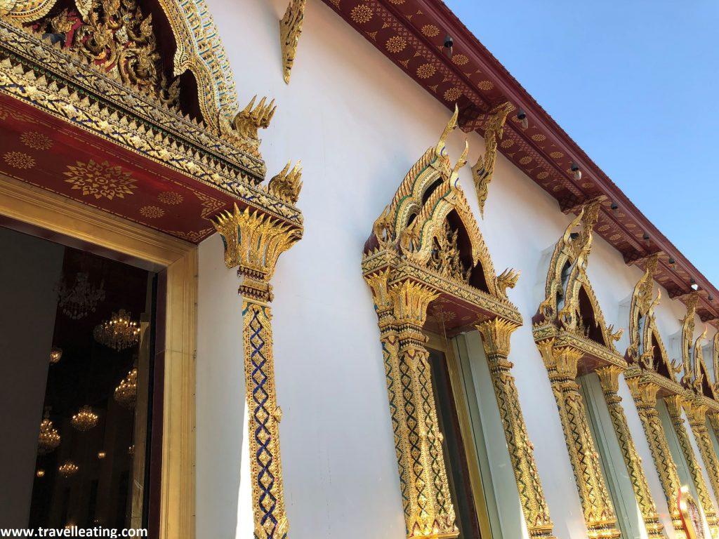 Fachada lateral de un templo blanco con ventanas ornamendadas con detalles dorados y rojos.