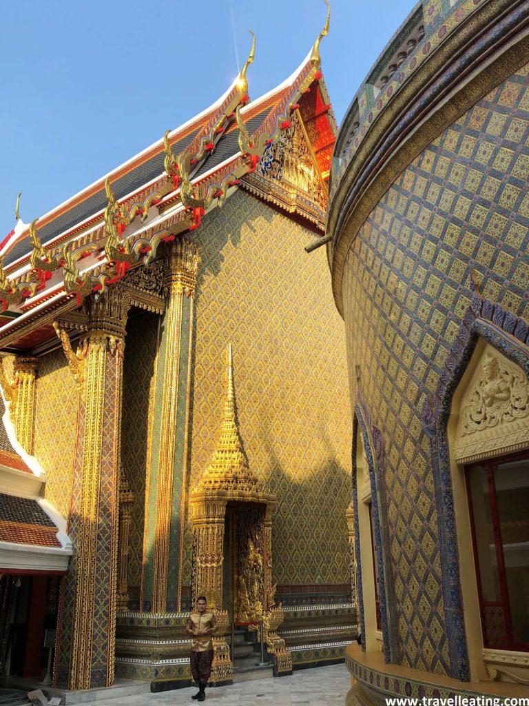 Patio interior de un templo tailandés en el que se ve el edificio central y uno de los laterales. Ambos destacan por su color dorado, aunque cada uno tiene detalles de colores, uno lila y el otro rojo.