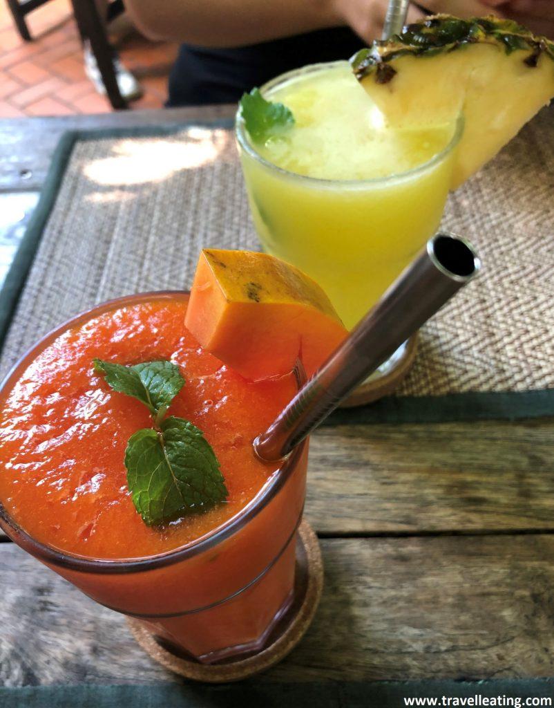 Vaso alargado con zumo de papaya servido con un trozo de papaya, dos hojas de menta y una pajita de acero y un vaso alargado con zumo de piña servido con un trozo de piña y otra pajita de acero.