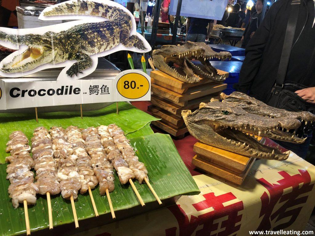 Puesto de comida de un mercado nocturno en el que tienen expuestos pinchos de carne de cocodrilo. Lo anuncia un cartel con una imagen de cocodrilo y varias cabezas de este animal que se encuentran también expuestas.