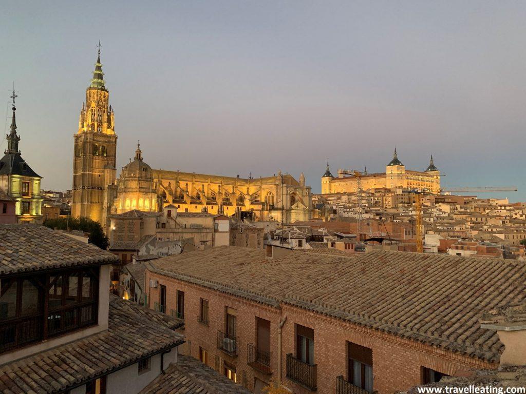 Vistas de la ciudad de Toledo al atardecer desde una azotea, con su Catedral y el Alcázar sobresaliendo por encima del resto de edificios.