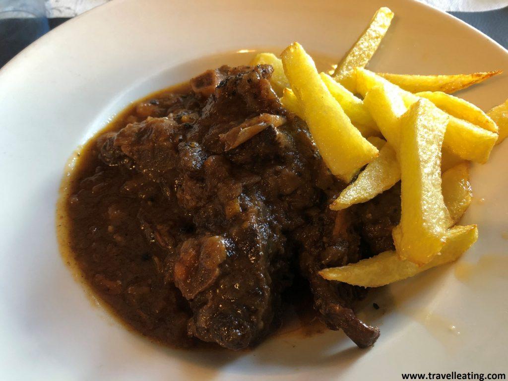 Tres trozos de cola de buey servida en un plato blanco con salsa de vino por encima y acompañada de patatas fritas.