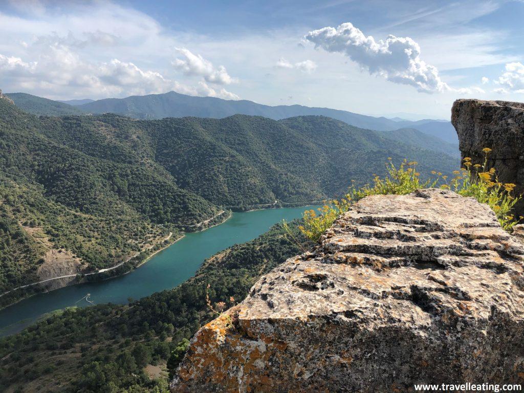 Pantano de color turquesa intenso rodeado de montañas verdes. La imagen está vista desde una zona rocosa.