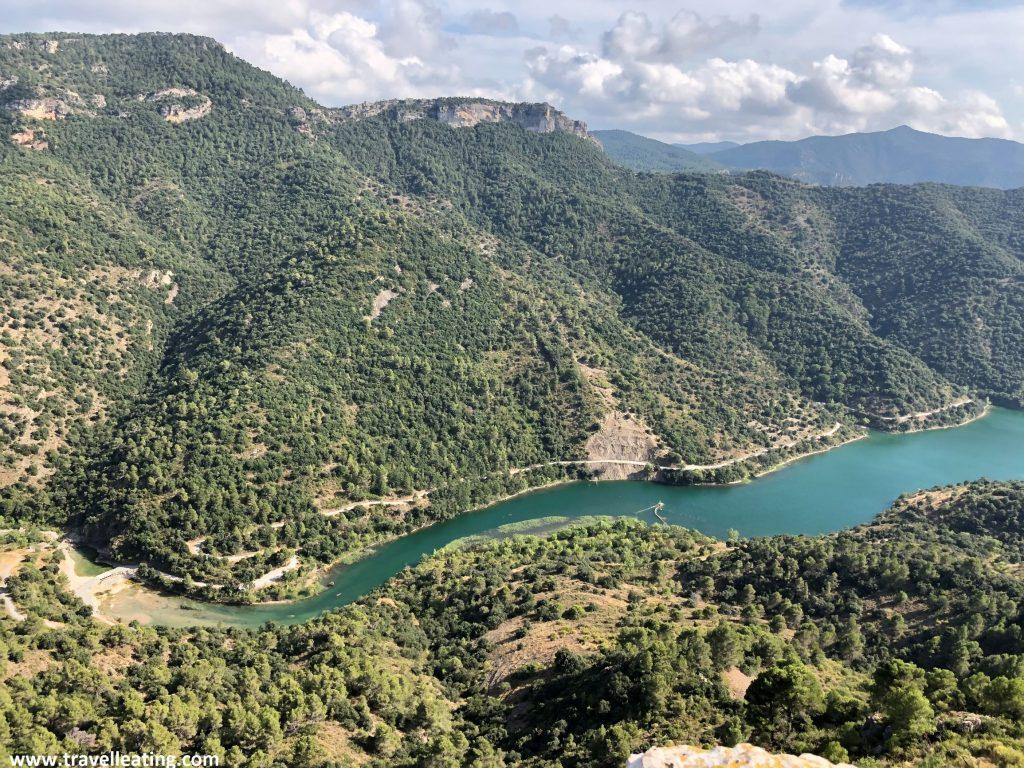Preciosas vistas de un río con aguas turquesas que corre sinuoso delante de unas montañas verdes.