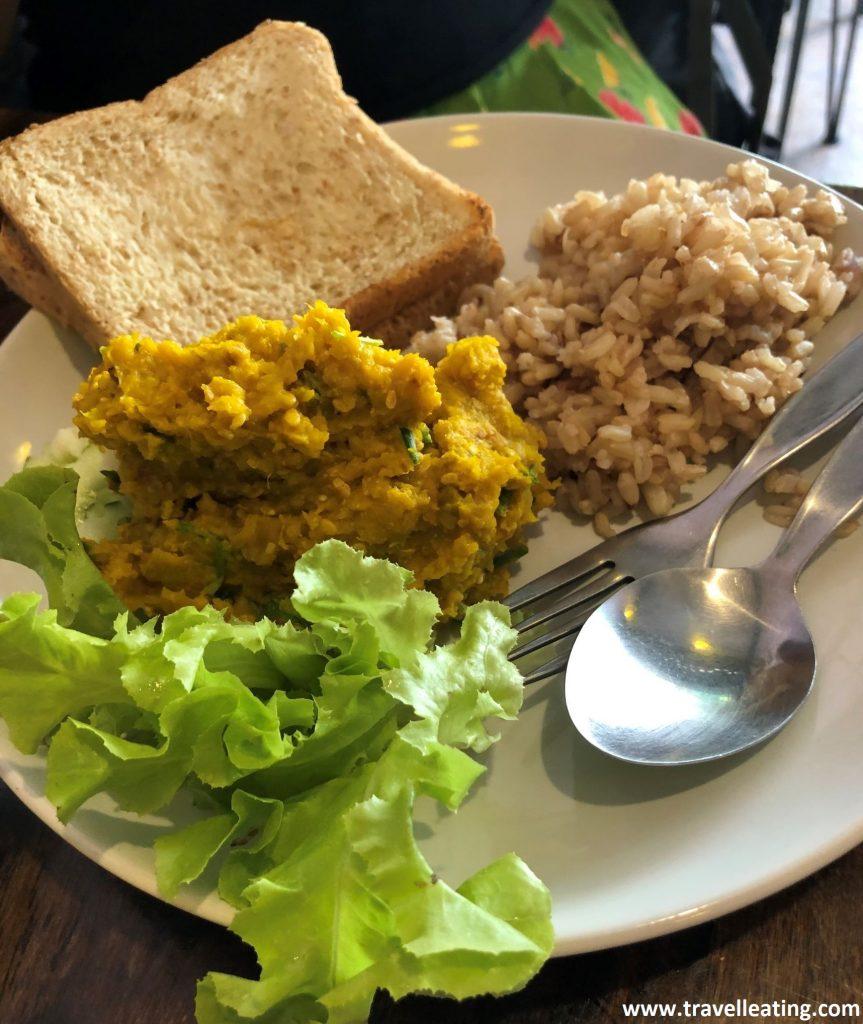 Plato de hummus de calabaza acompañado de lechuga, arroz y una tostada de pan de molde. Un ejemplo de que la gastronomía tailandesa siempre incluye el arroz.