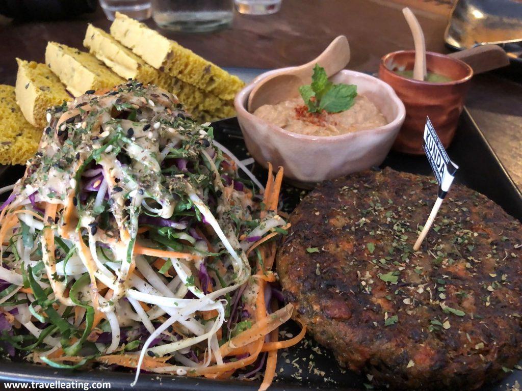 Plato combinado a base de una hamburguesa vegana, una ensalada hecha a tiras, hummus, salsa de iogurt y tostadas de pan casero de pipas.