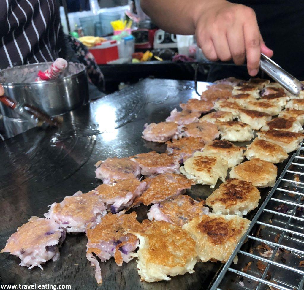 Plancha negra de un puesto de comida callejera sobre la cual reposan decenas de mini tortitas hechas con coco rallado, la mitad blancas y la otra mitad de un color morado.