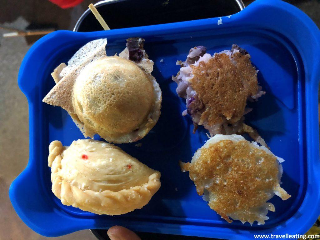 Tapa de tuper sobre la cual se ven cuatro dulces: a la derecha dos tortitas minis de coco, a bajo a la izquierda una mini empanada y arriba a la izquierda un pancake tailanés, como una bolita rellena de crema de coco.