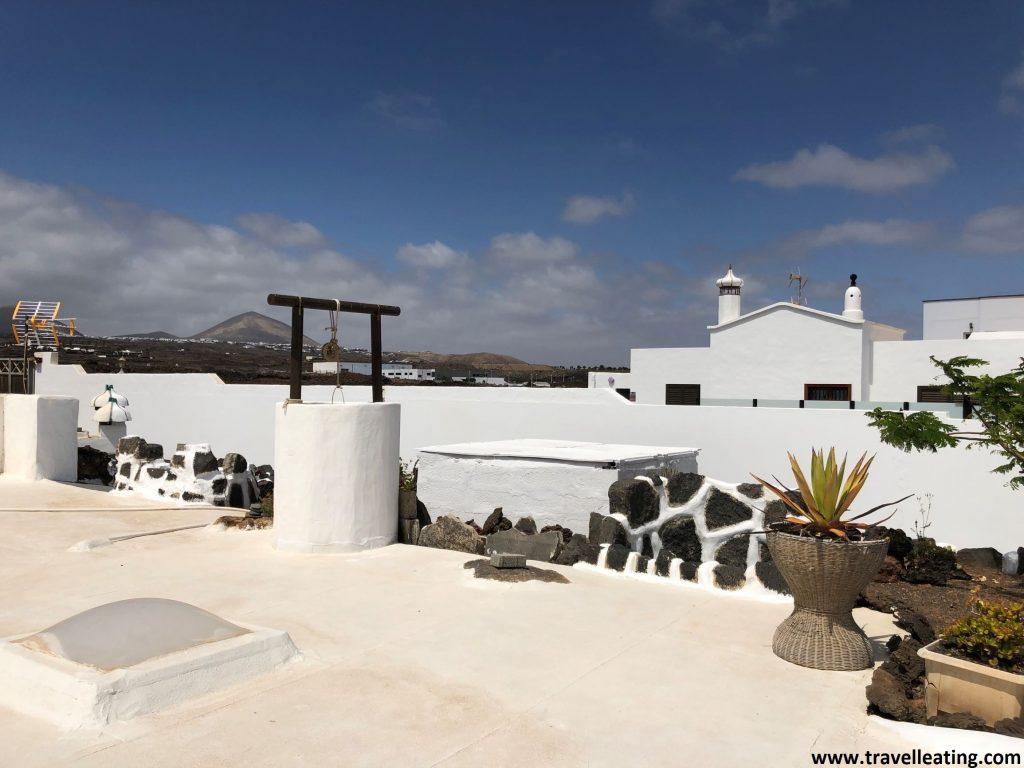 Preciosa entrada de una casa tradicional lanzaroteña, toda ella blanca. Presenta un pozo y varios cactus, y está rodeada de un precioso paisaje volcánico.