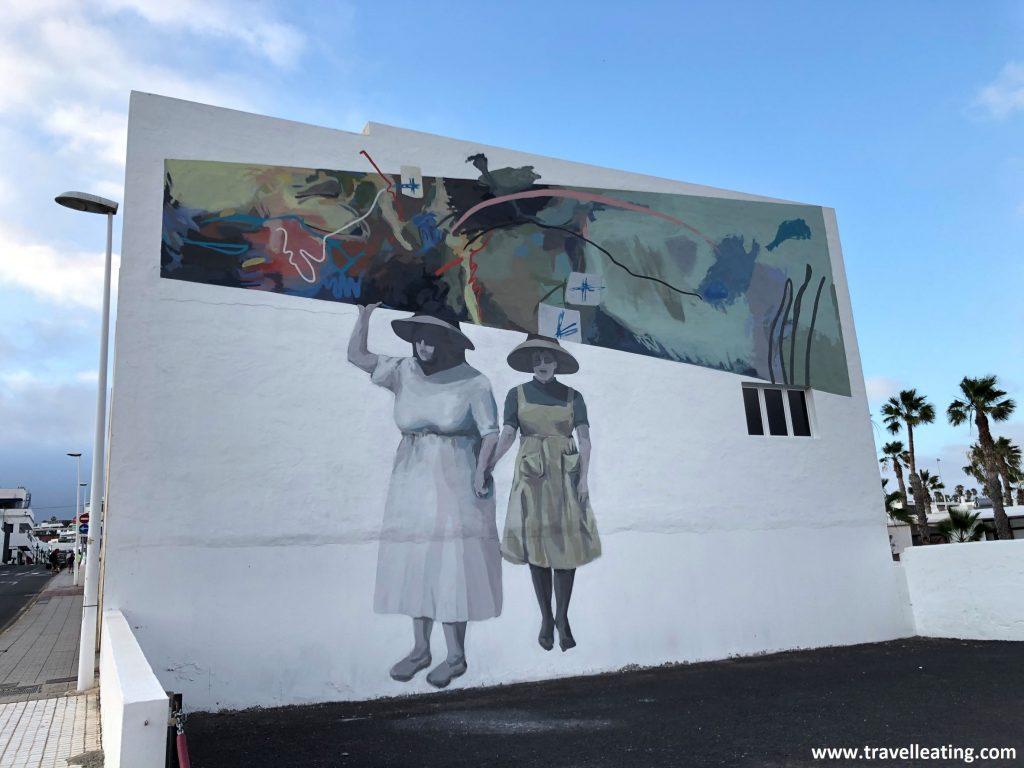 Mural hecho en una fachada de una casa blanca en el que se ven dos campesinas lanzaroteñas tradicionales, con sus vestidos y sus gorros de paja.