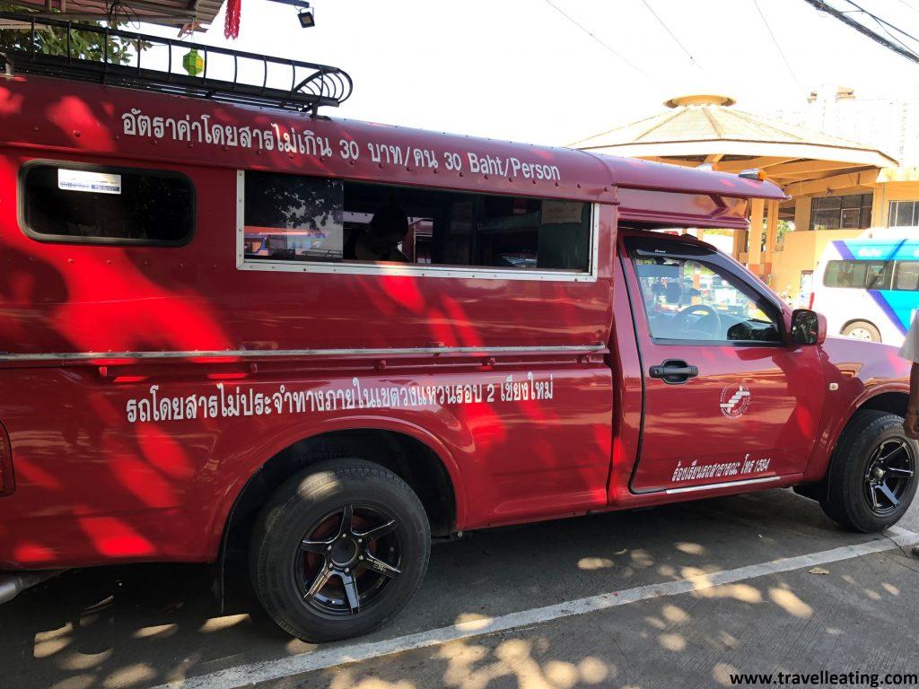 Camioneta roja alargada que lleva pasajeros en su interior.