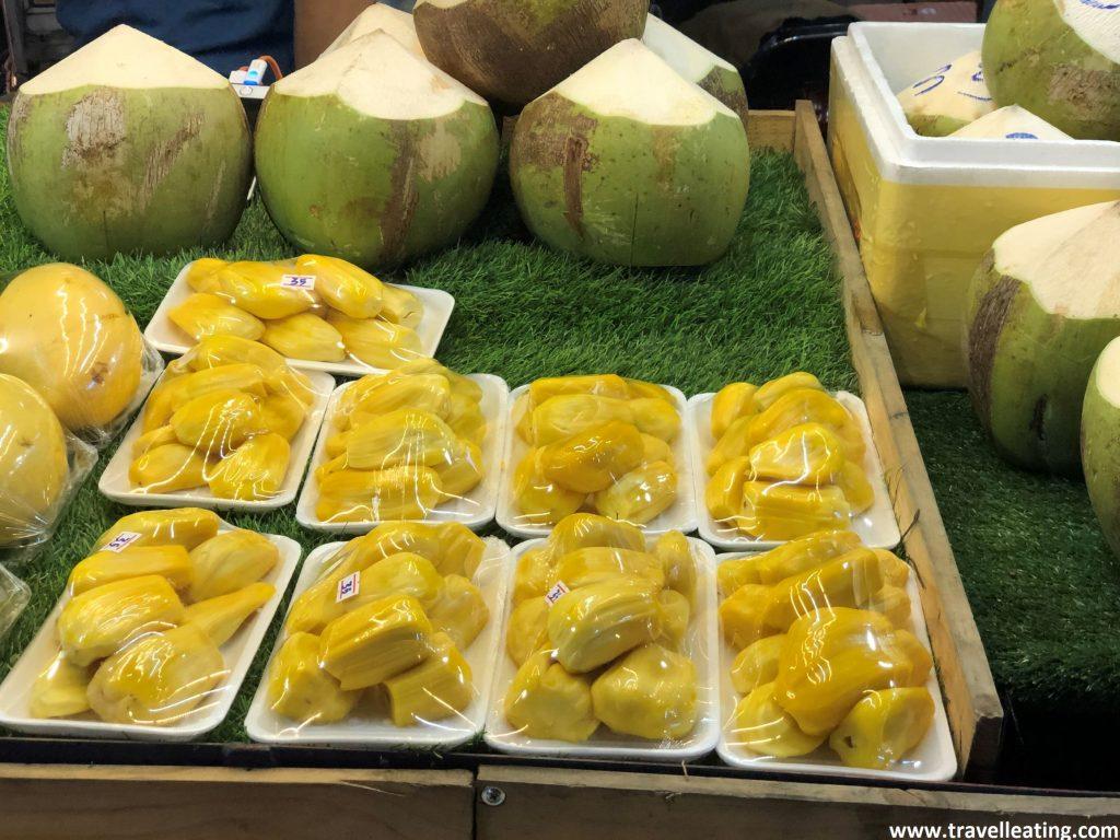Tienda callejera con durians y cocos frescos expuestos.