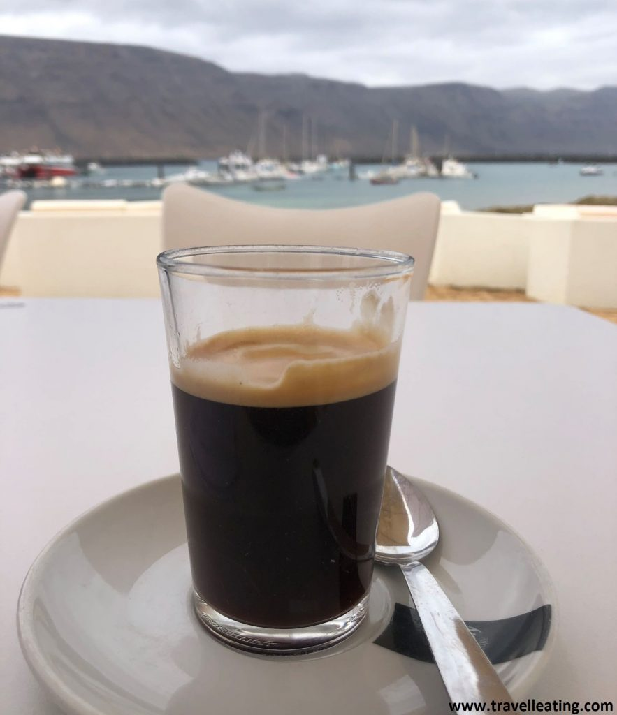 Café servido en una mesa con unas preciosas vistas de fondo de una playa y un puerto.