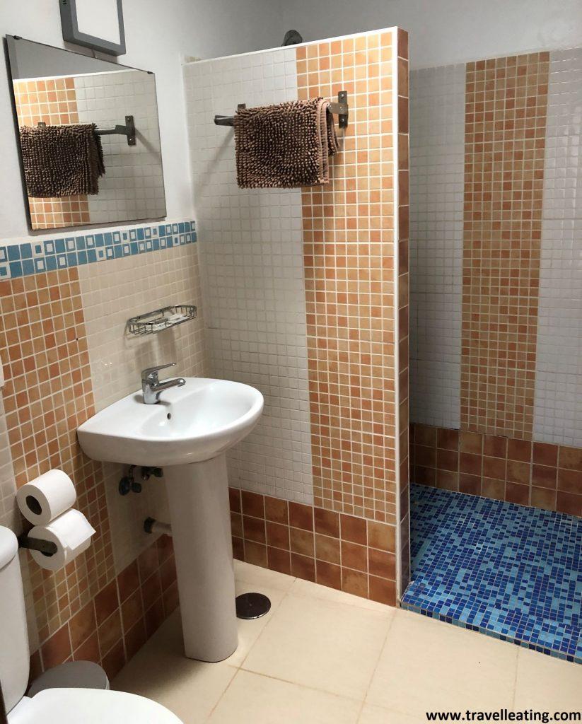 Baño sencillo con azulejos de colores varios (blancos, azules y anaranjados), con un espejo y una ducha de pie.