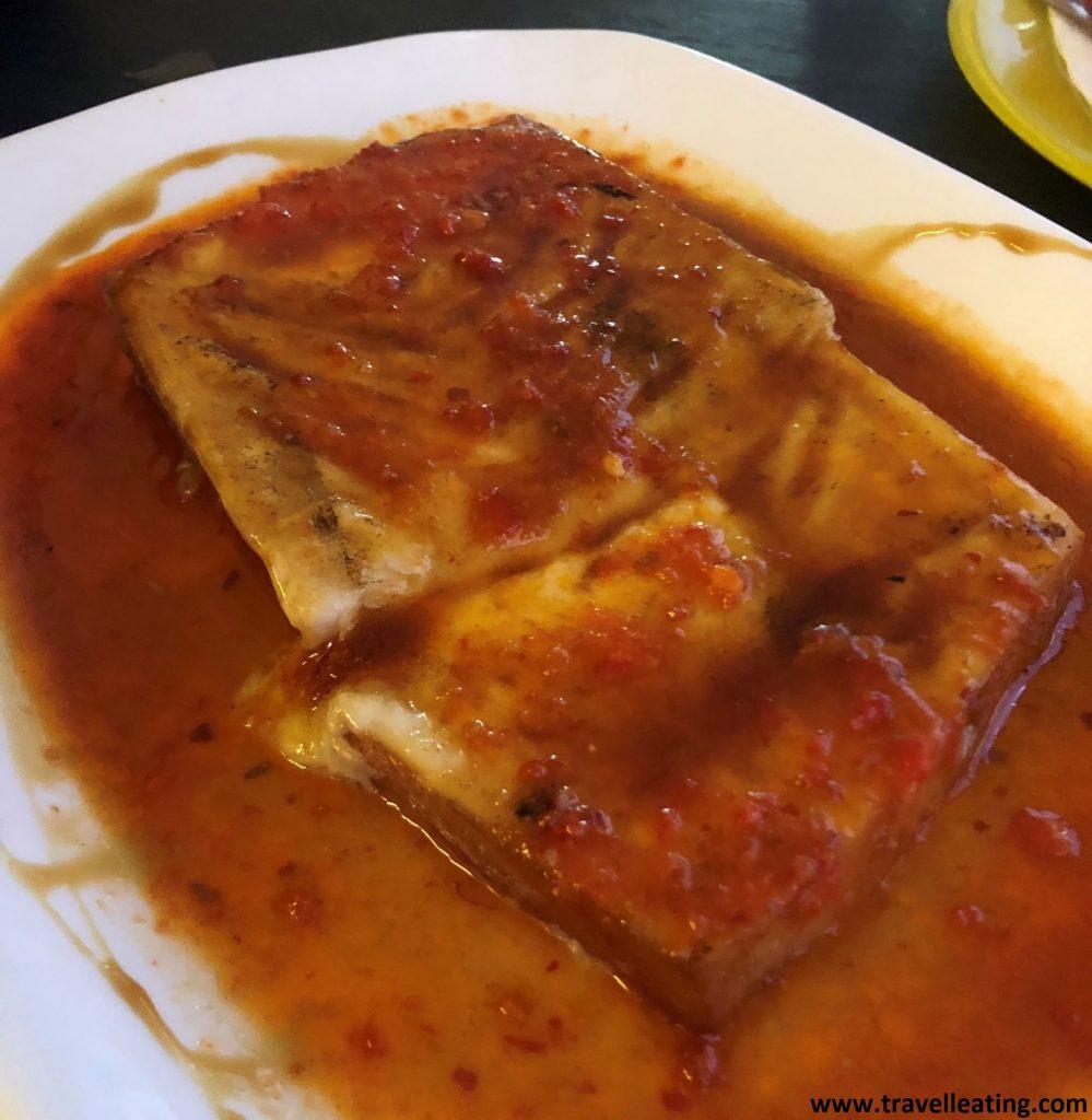 Plato blanco que presenta un queso ahumado hecho a la plancha cubierto de una salsa hecha con tomate y miel.
