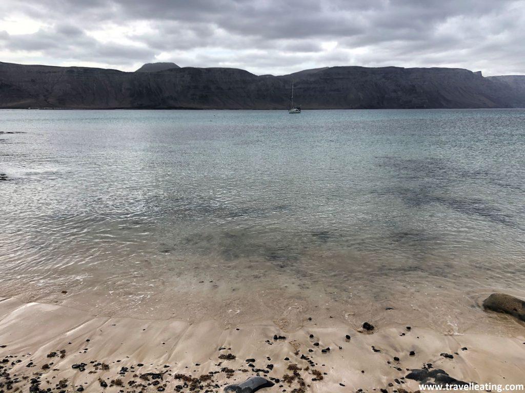 Orilla y aguas cristalinas de una playa al fondo de la cual vemos una isla que se alza.
