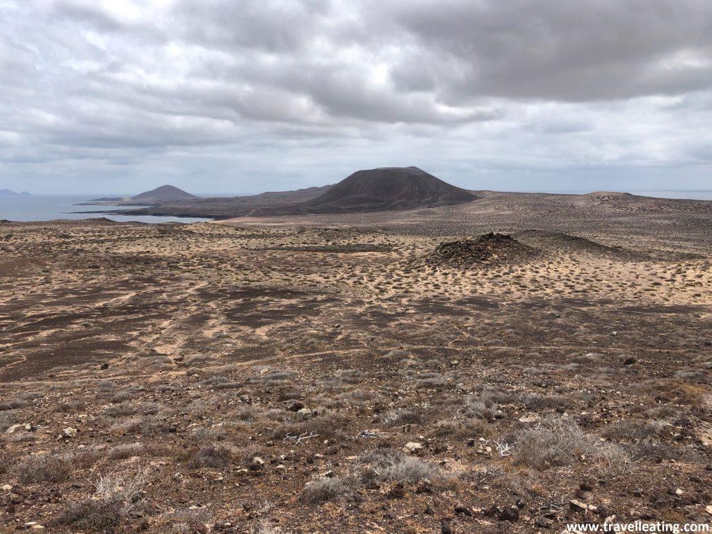 Increíbles vistas de la Isla de la Graciosa donde se ven extensiones desérticas de dunas, sus volcanes al fondo y el mar rodeándola.