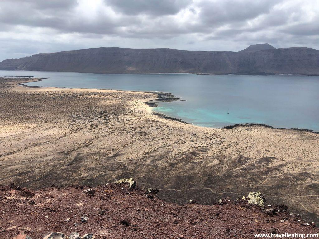 Vistas de la costa de una isla volcánica, con unas playas de agua turquesa, el mar y, al fondo, una isla con un gran risco.