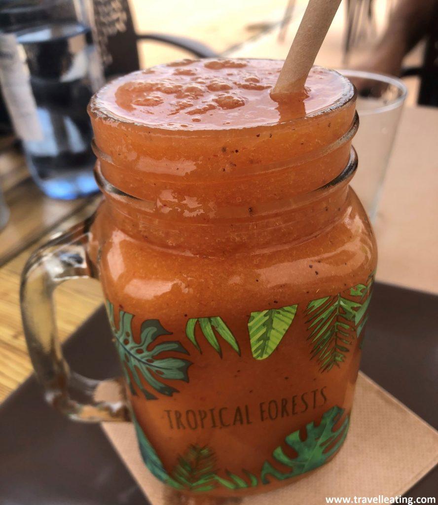 Vaso grande de smoothie que presenta un zumo natural de frutas de color rojizo-anaranjado.