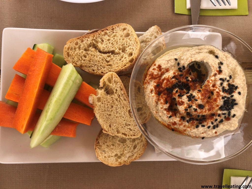 Pequeño bol de hummus acompañado de crudités de verduras y de pequeñas tostadas de pan.