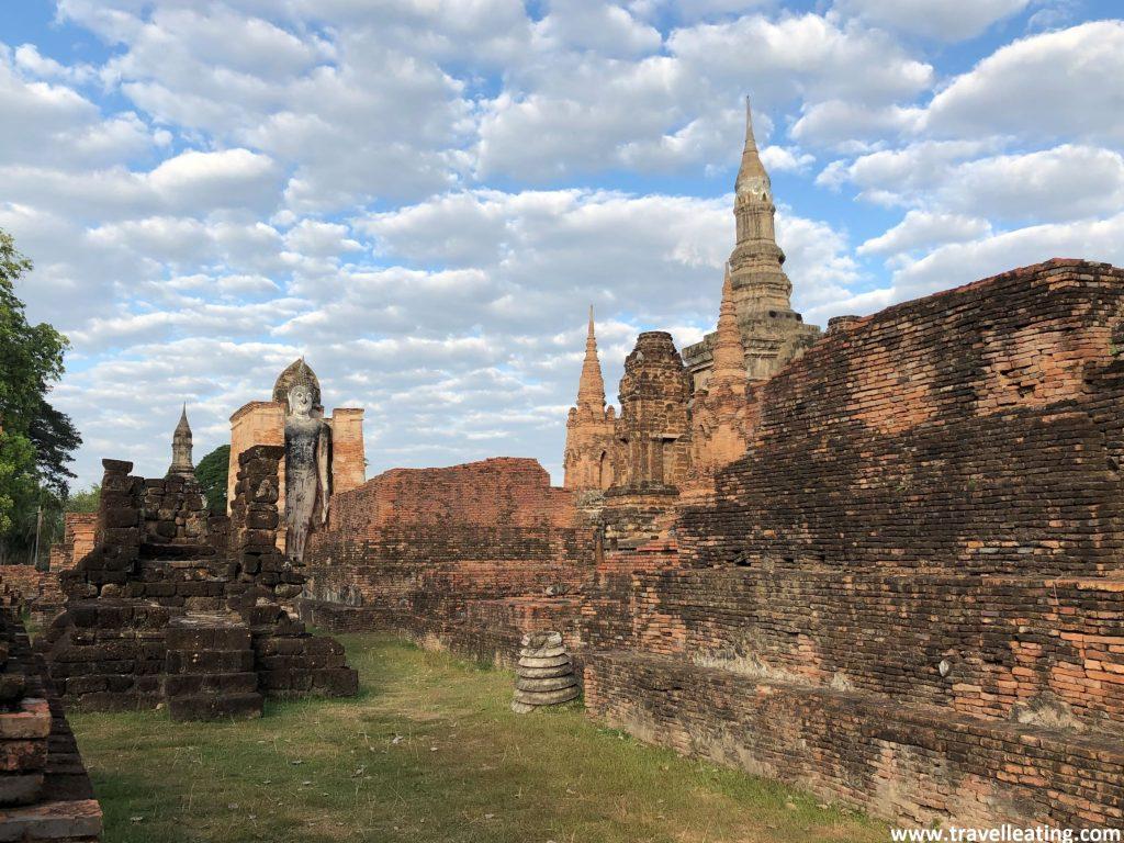 Ruinas del Parque Histórico de Sukhothai entre las que destaca un gran buda gris de pie. El cielo azul está repleto de pequeñas nubes esponjosas.