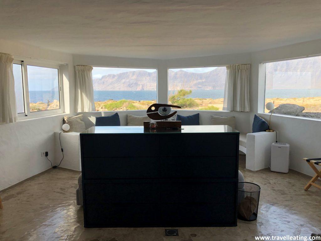 Precioso salón blanco con un sofá largo y detalles marineros que presenta un increíble ventanal con vistas al mar.