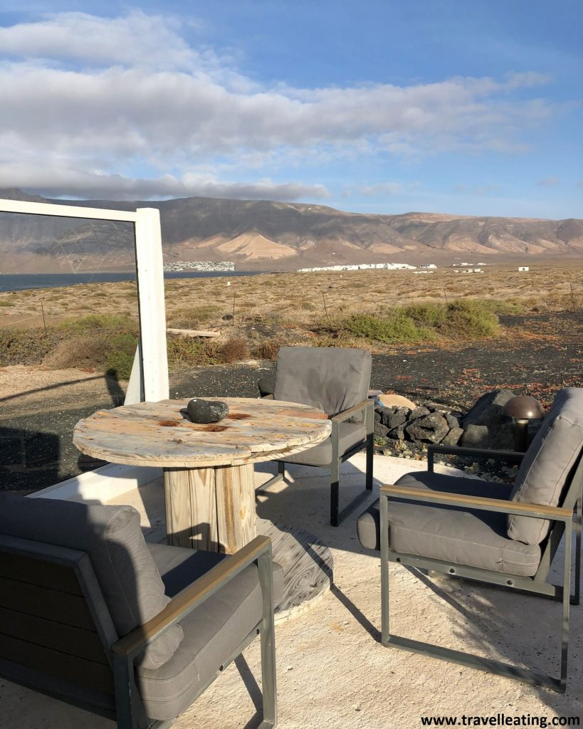 Preciosa terraza hecha a base de madera que dispone de una mesa y cuatro sillas con unas vistas espectaculares a un risco montañoso y el mar.