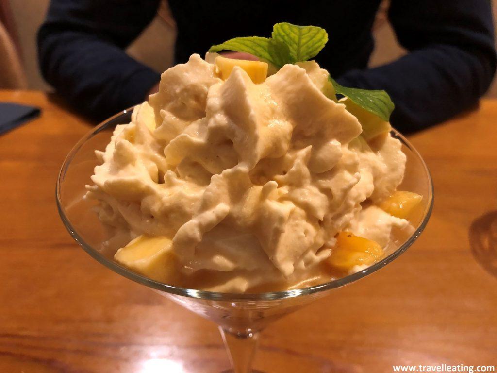 Copa de postre que presenta plátano confitado recubierto de mouse de gofio y coronado con una bola de helado de queso.