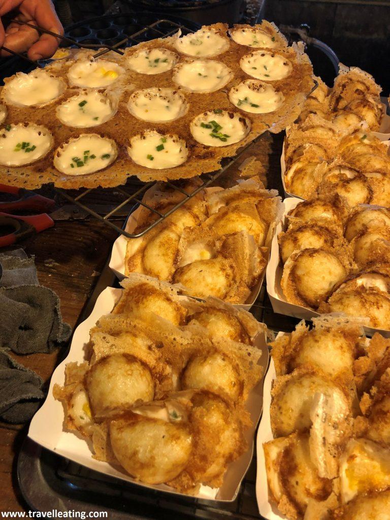 Pequeñas bandejas de cartón repletas de los pancakes tailandeses de coco, unas bolitas pequeñas y crujientes rellenas de crema de coco.