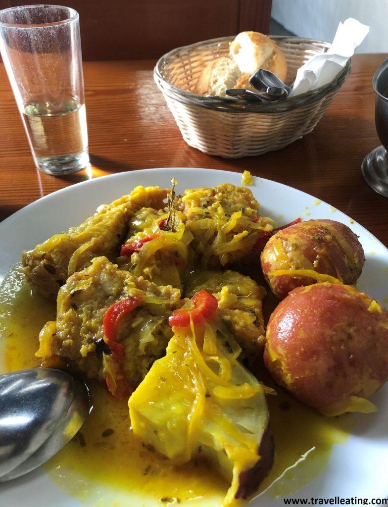 Plato con pescado en salsa con cebolla pochada y papas arrugadas, acompañado de pan.