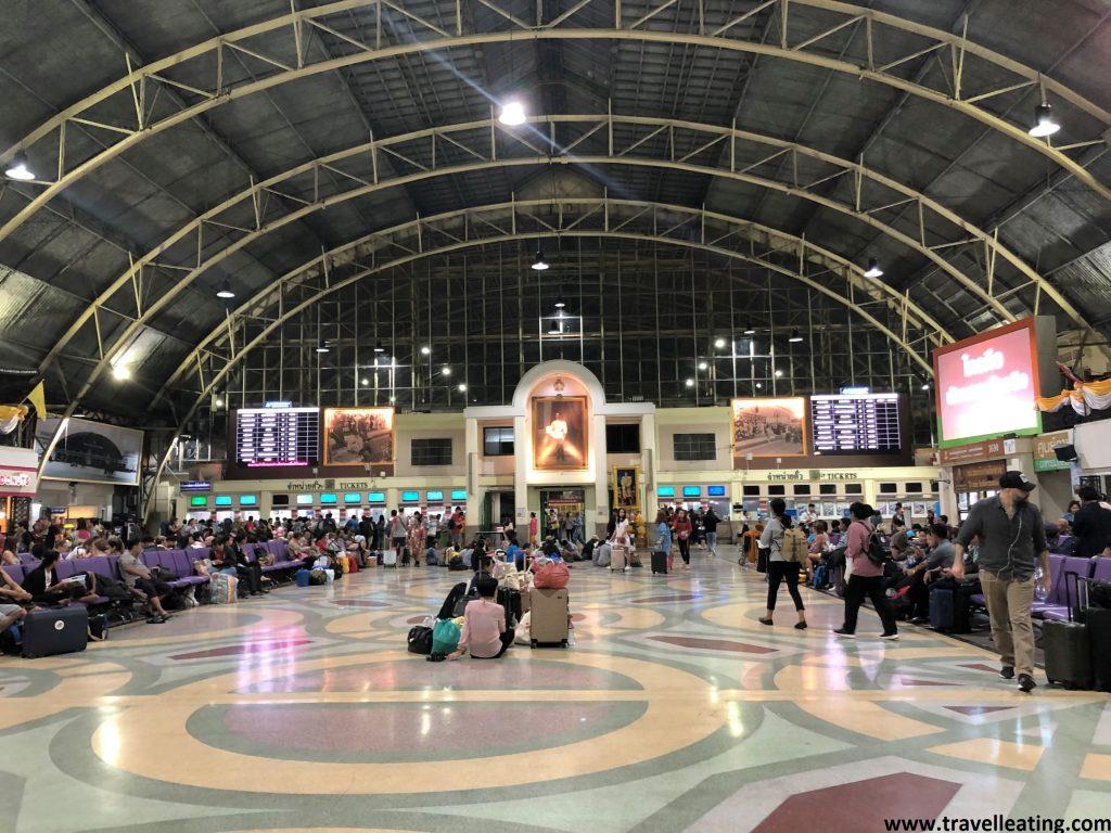 Sala principal de una de las estaciones de trenes más importantes de Bangkok, donde la gente comprando billetes o esperando.