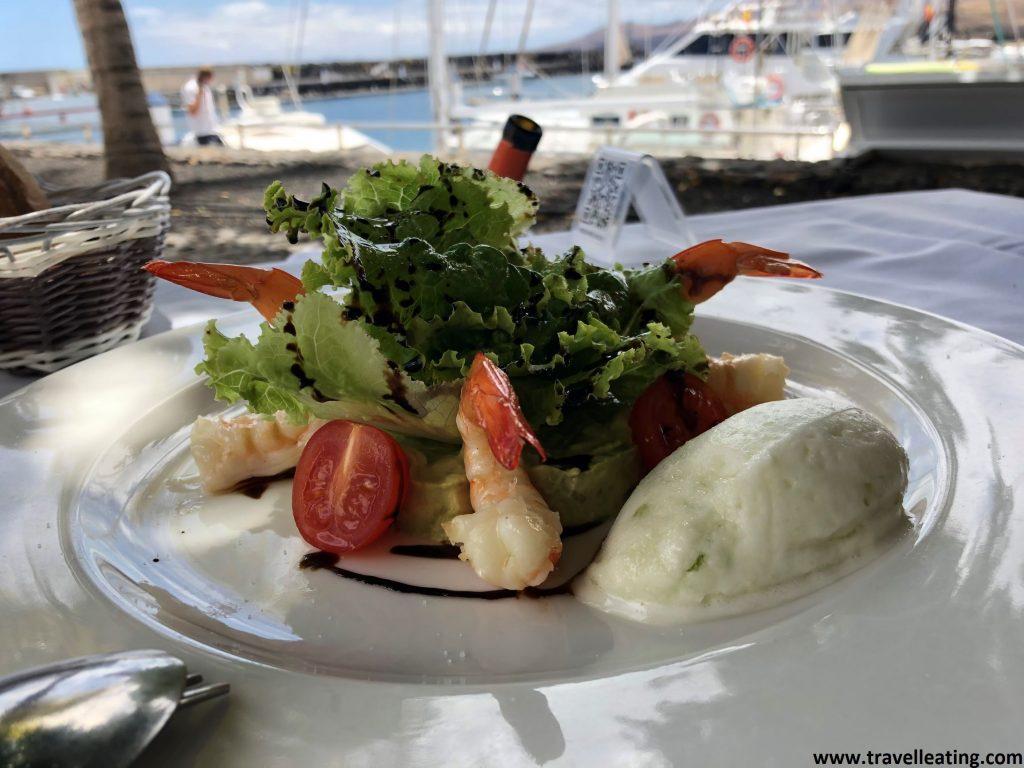 Plato que contiene un tartar de aguacate con langostinos y un helado de manzana, servido en una mesa con vistas al puerto. Uno de los platos recomendados de uno de los mejores restaurantes de Lanzarote.