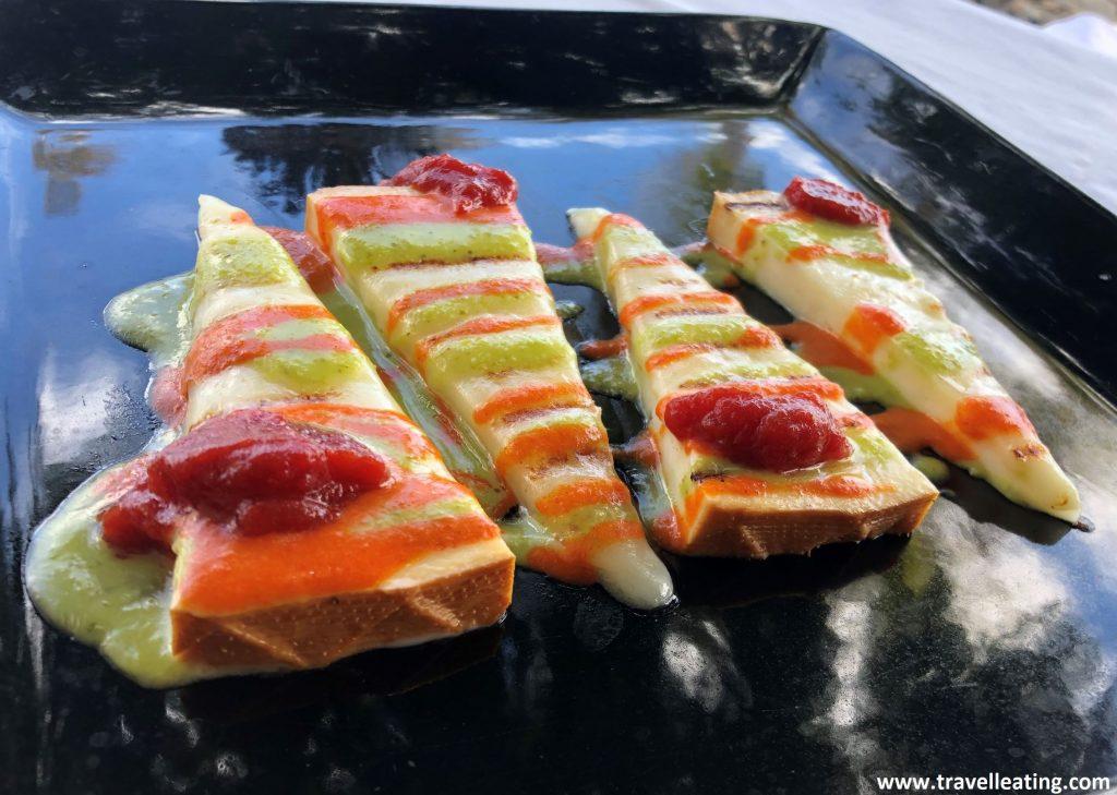 Plato rectangular negro en el que vemos cuatro trozos triangulares de queso hechos a la plancha y servidos con tomate confitado y mojo verde y rojo.