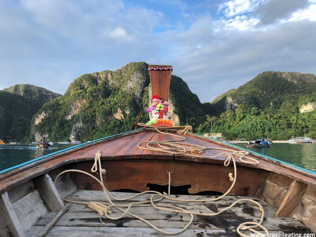 Primer plano de una long tal, la barca tradicional de madera de Tailandia, ante la cual se ve el mar y las piedras calizas de las Phi Phi. Una buena opción para viajar por Tailandia
