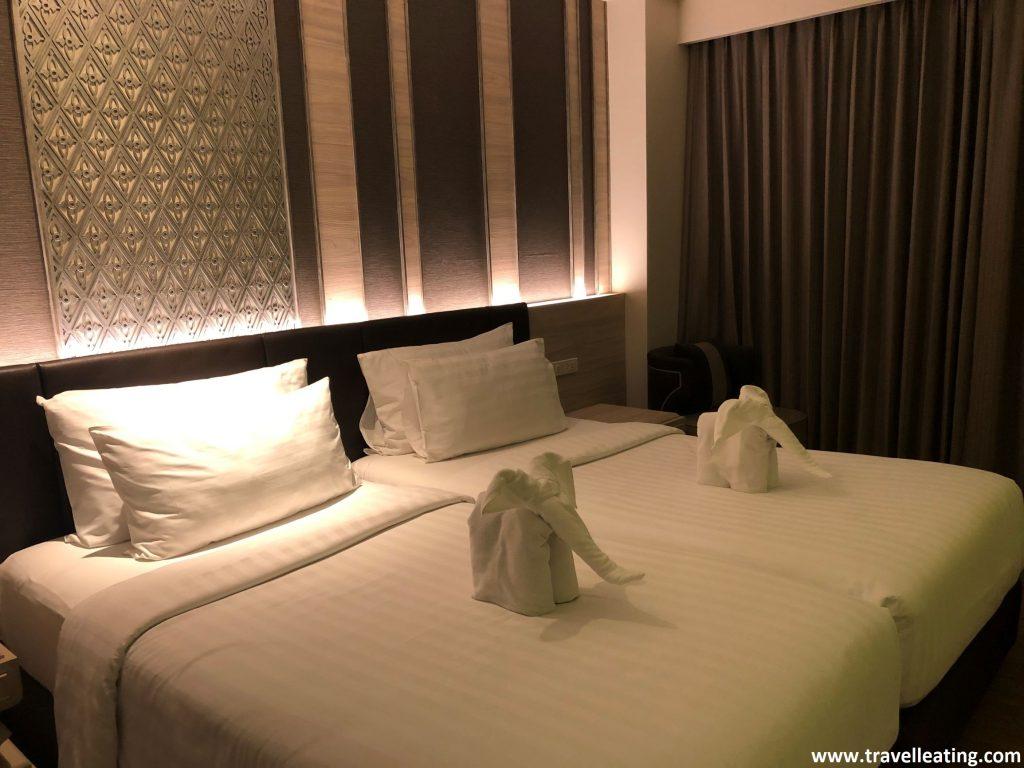 Habitación doble de hotel con dos camas y dos figuras de elefantes hechas con las toallas.