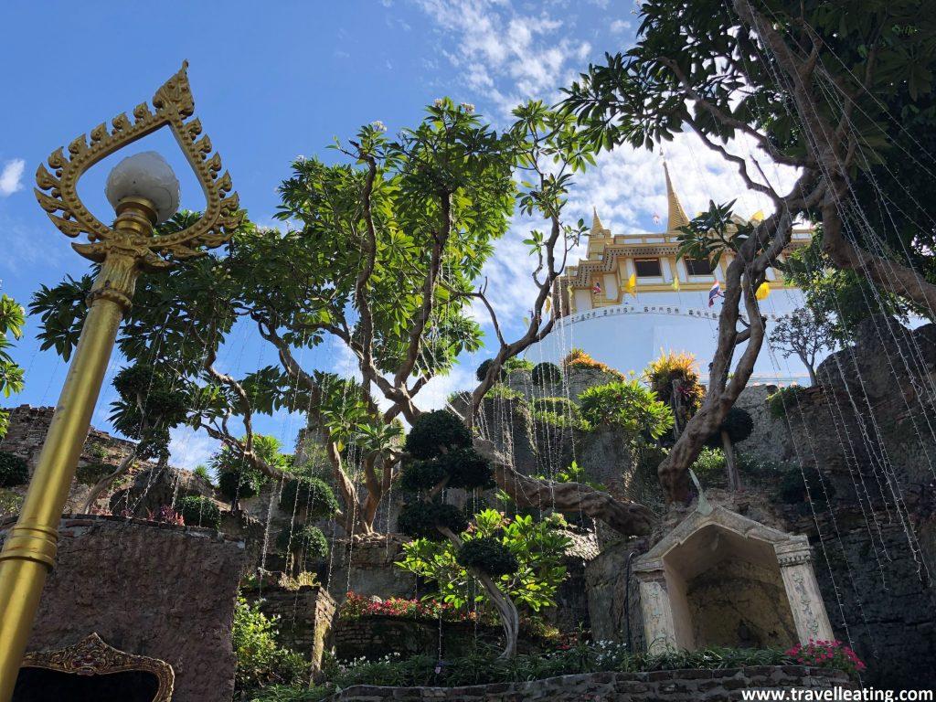 Fuente rodeada de árboles tras los cuales se contempla un templo blanco con detalles dorados en lo alto de un monte. Es el Golden Mount Temple, uno de los imprescindibles de Bangkok.