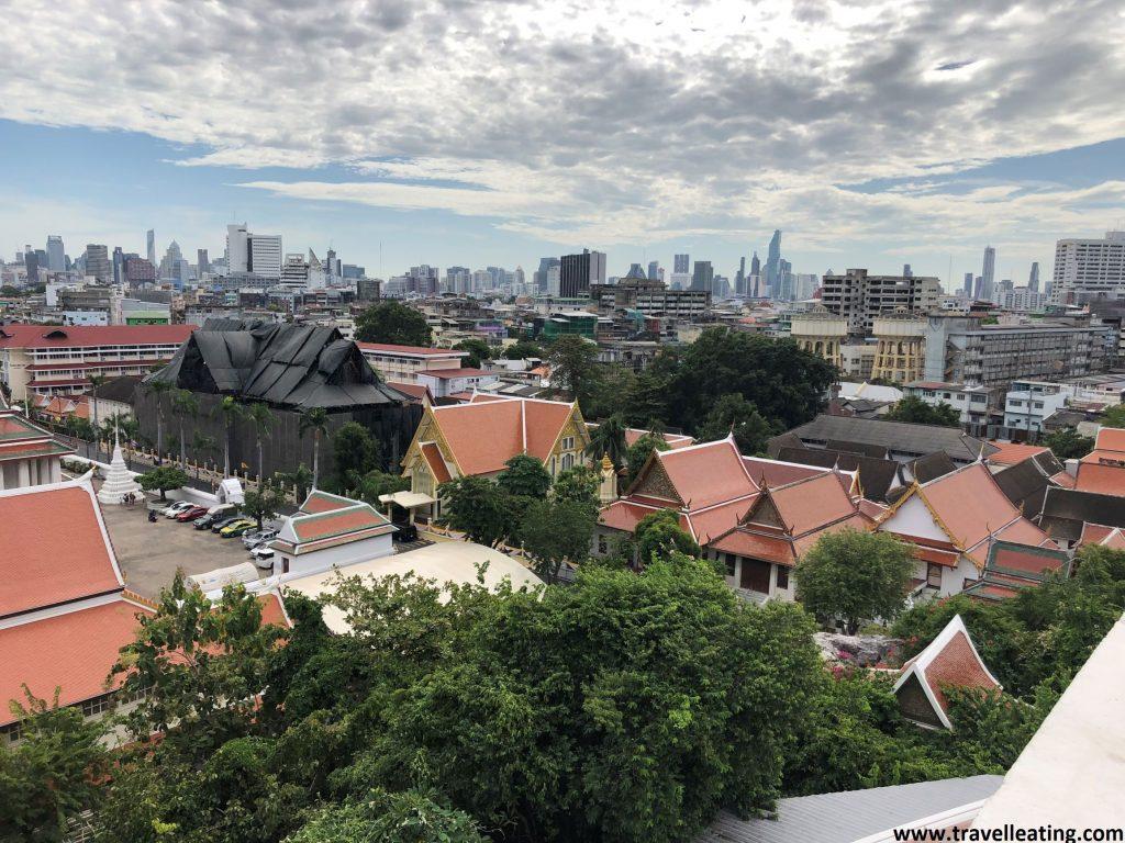 Preciosas vistas de la ciudad de Bankok en la que destacan en primera linea un conjunto de edificios con tejados anaranjados, mientras que en el fondo destacan grandes edificios altos y modernos.